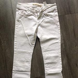 White jeans with designs on knee area.